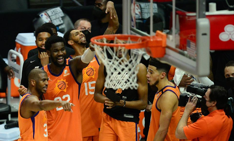 Jun 30, 2021; Los Angeles, California, USA; Phoenix Suns guard Chris Paul (3) center Deandre Ayton (22) guard Cameron Payne (15) and guard Devin Booker (1) celebrate the 130-103 series victory against the Los Angeles Clippers in game six of the Western Conference Finals for the 2021 NBA Playoffs at Staples Center. Mandatory Credit: Gary A. Vasquez-USA TODAY Sports ORG XMIT: IMAGN-453346 ORIG FILE ID:  20210630_gav_sv5_073.jpg