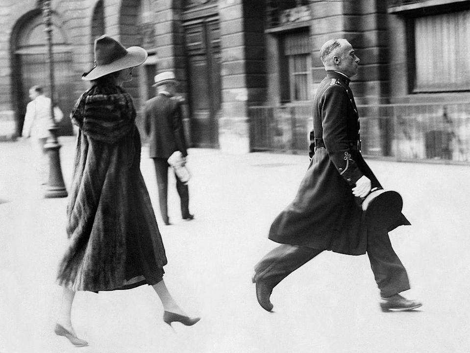 <p>Dietrich, pictured here as the epitome of European elegance, is escorted by a porter into a fashion house in Paris draped in an almost floor-length fur coat with a wide-brim hat. </p>