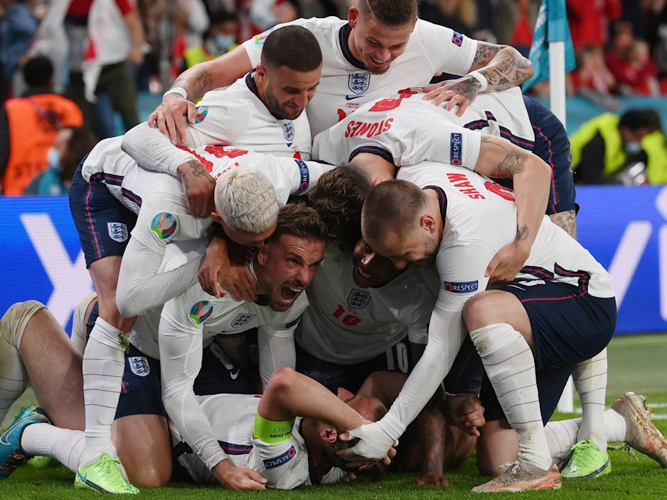 England's Harry Kane, bottom, celebrates with his teammates after scoring his side's second goal during the Euro 2020 soccer semifinal match between England and Denmark at Wembley stadium in London (AP)