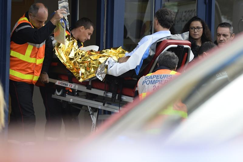 Firemen carry a man injured in the coach accident on October 23, 2015 in Puisseguin, southwestern France (AFP Photo/Jean-Pierre Muller)