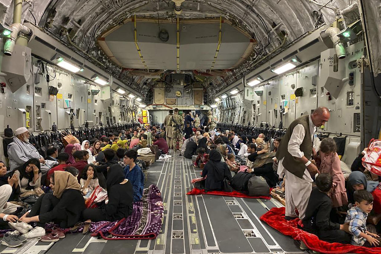 Afghan people sit inside a U.S. military aircraft to leave Afghanistan, at the military airport in Kabul on August 19, 2021. (Shakib Rahmani/AFP via Getty Images)