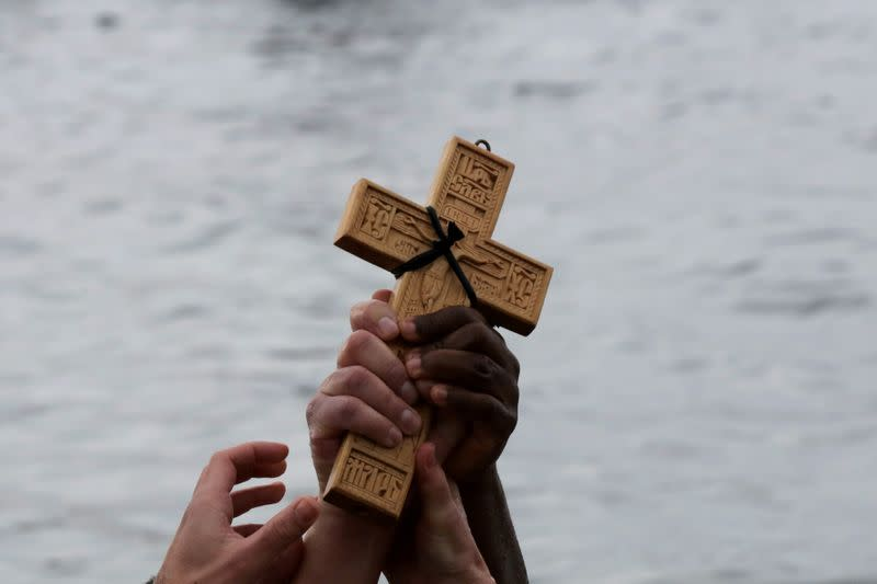 FILE PHOTO: Orthodox faithful raise a wooden crucifix during Epiphany day celebrations in the southern suburb of Faliro in Athens