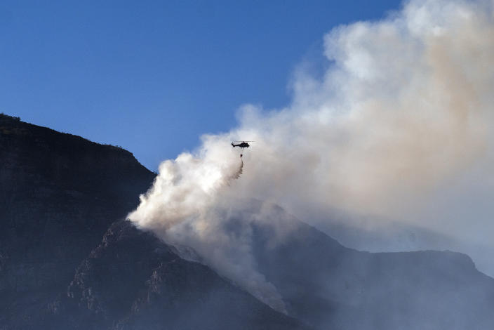 A South African military helicopter drops his water load on the top of Table Mountain in Cape Town, South Africa, Tuesday April 20, 2021. Fire crews worked for a third day to extinguish a wildfire on the slopes of Cape Town's Table Mountain on Tuesday as the city came to terms with the damage caused by what officials have described as one of the area's worst blazes in years. (AP Photo/Jerome Delay)