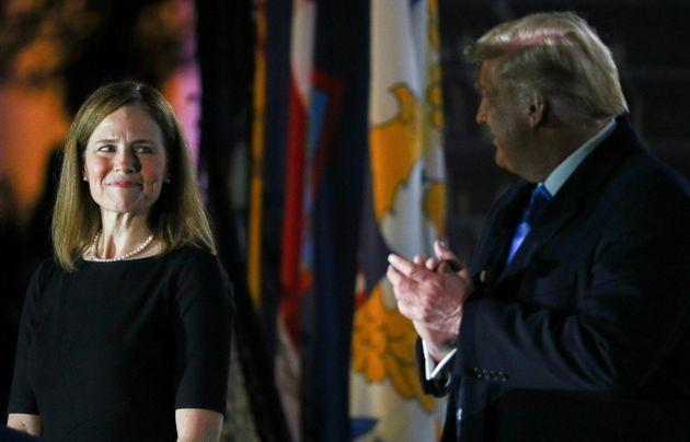 Judge Amy Coney Barrett looks over at US President Donald Trump as she is sworn in to serve as an associate justice of the Supreme Court.