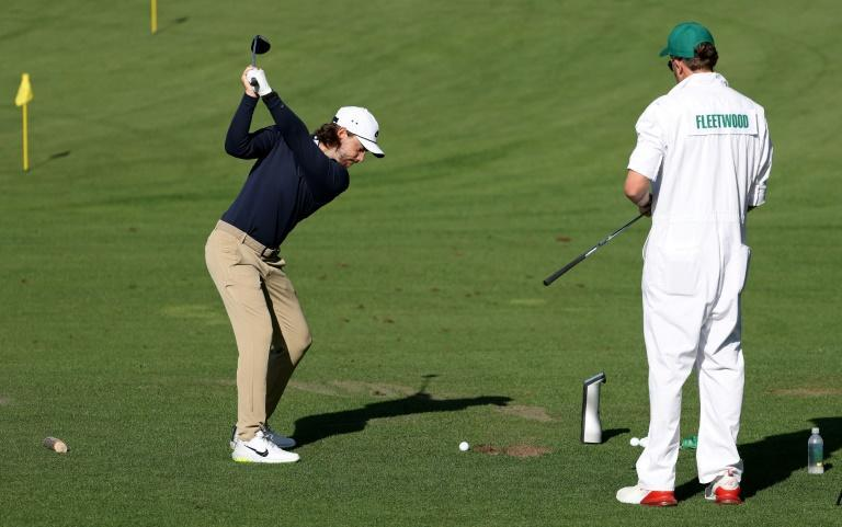 England's Tommy Fleetwood takes a swing on the practice range while caddie Ian Finnis watches on Monday at the Masters