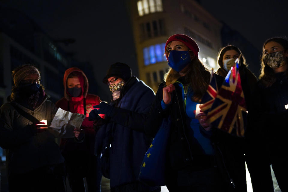British citizens, who live in Belgium, hold candles and Union flags during an anti Brexit vigil in front of the UK mission building at the European quarter in Brussels, Thursday, Dec. 31, 2020. On Thursday, the United Kingdom is finally moving out. At 11pm London time, midnight at EU headquarters in Brussels, Britain will economically and practically leave the 27-nation bloc, 11 months after its formal political departure. (AP Photo/Francisco Seco)