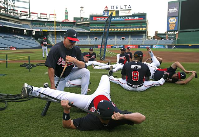 Atlanta Braves manager Fredi Gonzalez, kneeling, talks with outfielder Joey Terdoslavich as players stretch before practice Wednesday, Oct. 2, 2013, in Atlanta. The Braves are scheduled to play the Los Angeles Dodgers in Game 1 of baseball's NL division series on Thursday. (AP Photo/Atlanta Journal Constitution, Jason Getz)