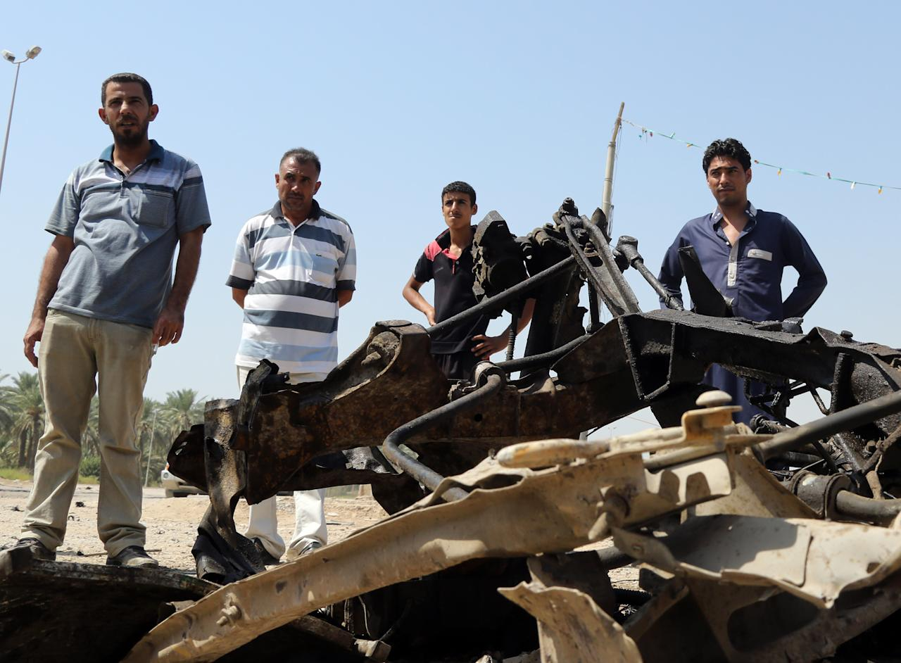 Citizens inspect the wreckage of a car bomb, in the town of Hafriyah, outside Kut, 100 miles (160 kilometers) southeast of Baghdad, Iraq, Sunday, Sept. 15, 2013. A new wave of insurgent attacks, mostly car bombs targeting Shiite-dominated cities in central and southern Iraq, killed and wounded scores of people, officials said. (AP Photo/ Hadi Mizban)