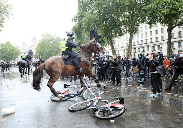 A mounted police officer struggles to avoid two public hire bikes on the ground during a Black Lives Matter protest rally in London (PA)