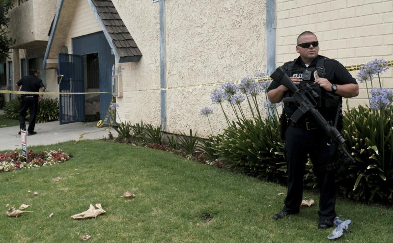 A Los Angeles police officer stands outside of an apartment where a shooting occurred in the Canoga Park area of Los Angeles on Thursday, July 25, 2019.  Police say a gunman shot five people, killing three, in two attacks in Los Angeles before he tried to rob someone outside a bank. (Dean Musgrove/The Orange County Register via AP)
