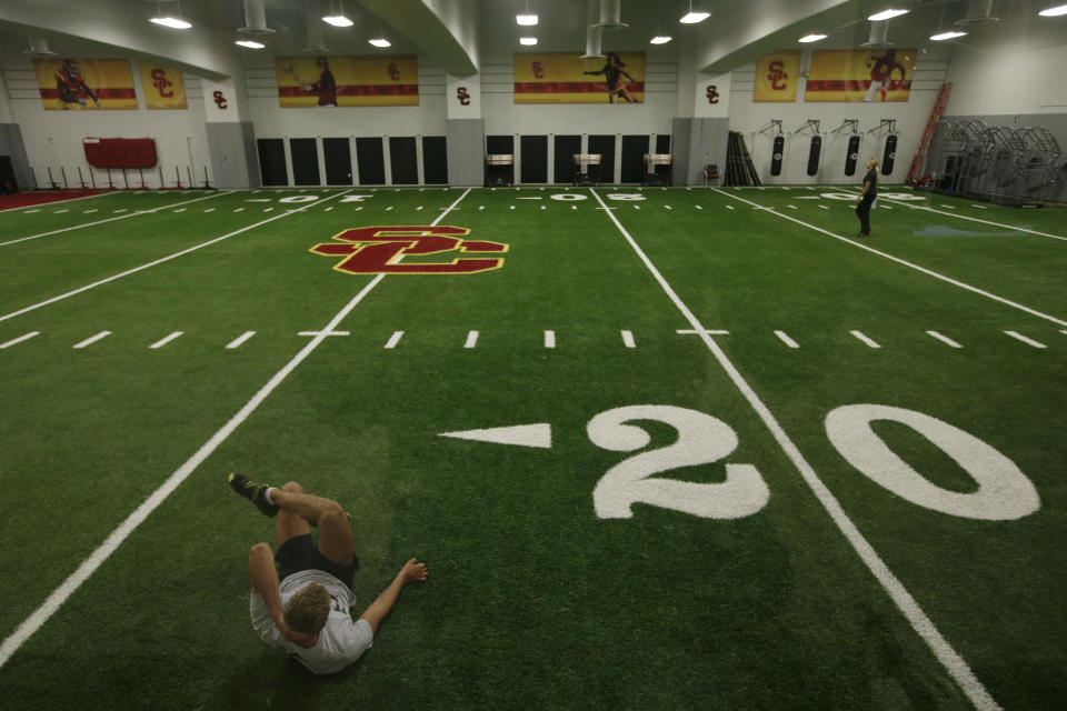 In this Sept. 5, 2013 photo, a student athlete works out on the indoor practice field at the John McKay Center, an athletic facility on the University of Southern California campus  in Los Angeles. Call them football palaces, and no college football program can call itself big-time without one that will leave recruits wide-eyed. (AP Photo/Jae C. Hong)