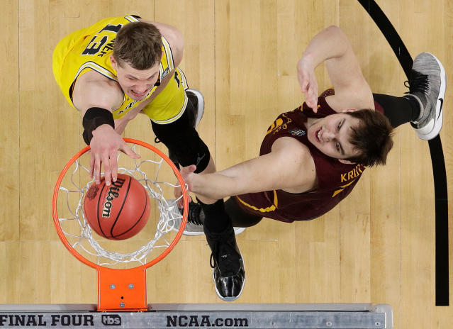 Michigan's Moritz Wagner (13) dunks over Loyola-Chicago's Cameron Krutwig (25) during the first half in the semifinals of the Final Four NCAA college basketball tournament, Saturday, March 31, 2018, in San Antonio. (AP Photo/David J. Phillip)