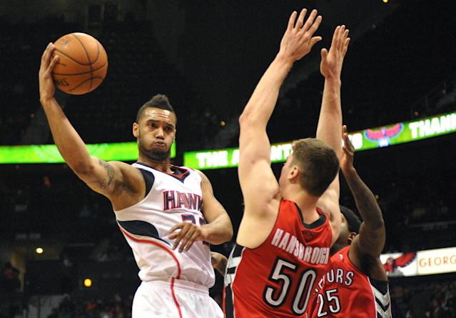 Atlanta Hawks' Mike Scott, left, passes around Toronto Raptors' Tyler Hansbrough (50) and John Salmons (25) in the first half of their NBA basketball game Tuesday, March 18, 2014, in Atlanta. (AP Photo/David Tulis)