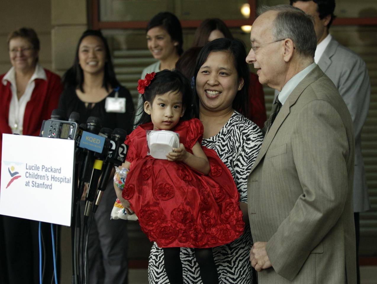 Ginady Sabuco, center, holds her daughter Angelina next to surgeon Gary Hartman, at right, at Lucile Packard Children's Hospital, Monday, Nov. 14, 2011 in Stanford, Calif. Angelina and twin sister Angelica, who were born joined in the chest and abdomen, are preparing to go home after an intricate surgery to separate them by a group of Lucile Packard doctors. (AP Photo/Marcio Jose Sanchez)