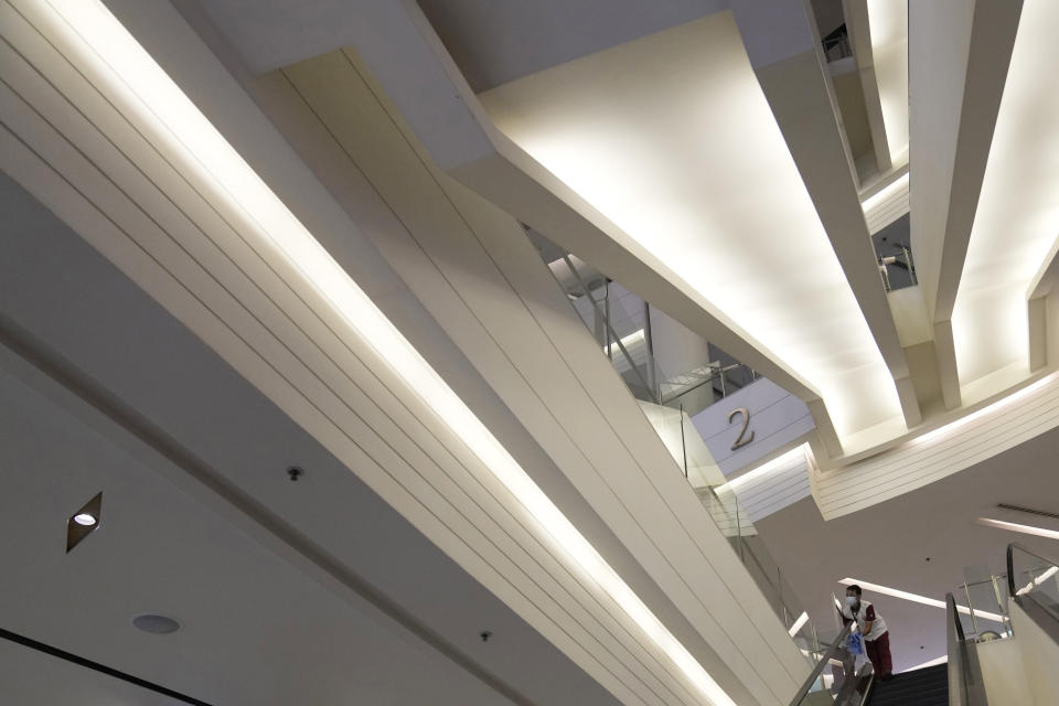 A worker cleans an escalator during the opening at the Paragon shopping mall in Bangkok, Thailand, Wednesday, Sept. 1, 2021. Thailand to ease business lockdown measures in the capital and provinces where restrictions have been implemented since mid-July. Malls, hair salons, foot massage parlors, and parks will be allowed to re-open, as well as restaurants for dine-in services but maintained at 50% capacity. (AP Photo/Sakchai Lalit)