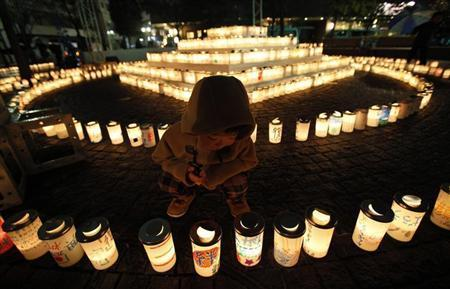 A boy looks at a candle light at a memorial held in remembrance of victims of the March 11, 2011 earthquake and tsunami in Koriyama