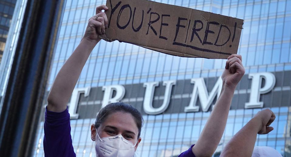 "A woman holds a ""you're fired"" sign outside a Trump tower."