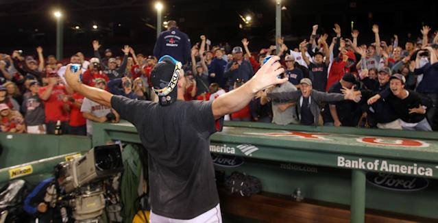 Boston Red Sox catcher Ryan Lavarnway celebrates with fans after the Red Sox clinched the AL East title with a 6-3 win over the Toronto Blue Jays in a baseball game at Fenway Park, Friday, Sept. 20, 2013, in Boston. (AP Photo/Charles Krupa)