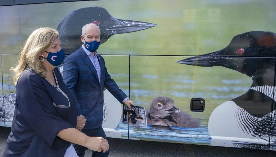 O'Toole and his wife walk past a mural on his campaign bus that shows loons.