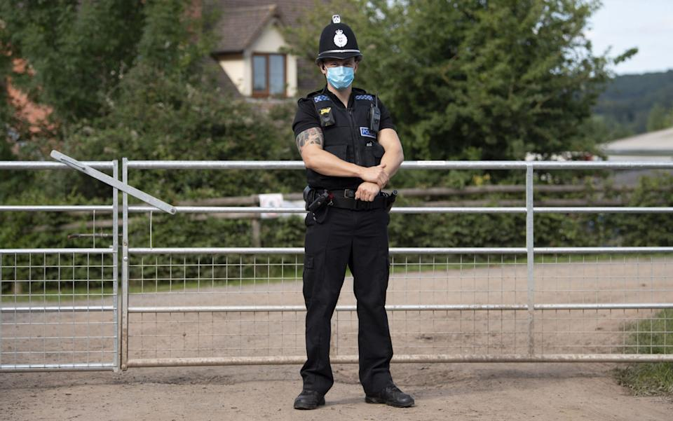 A police officer stands at the entrance to the AS Green & Co farm - Matthew Horwood/Getty