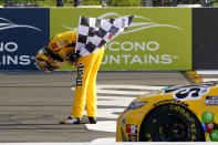 Kyle Busch takes a bow with the checker flag after winning a NASCAR Cup Series auto race at Pocono Raceway, Sunday, June 27, 2021, in Long Pond, Pa. (AP Photo/Matt Slocum)