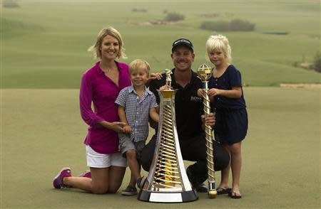 Henrik Stenson of Sweden poses with his trophies and his family after winning the DP World Tour Championship in Dubai November 17, 2013. REUTERS/Caren Firouz