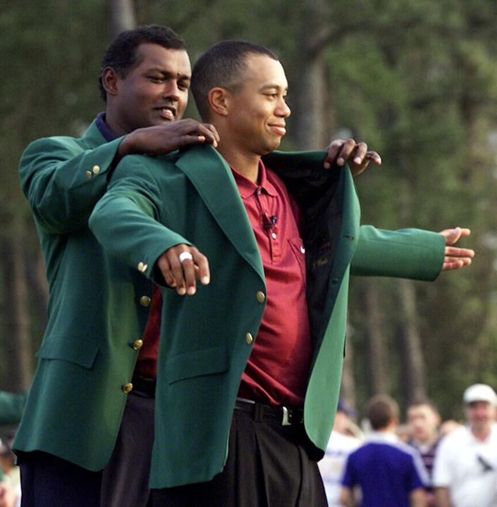 Tiger Woods receiving his Masters green jacket from champion Vijay Singh.