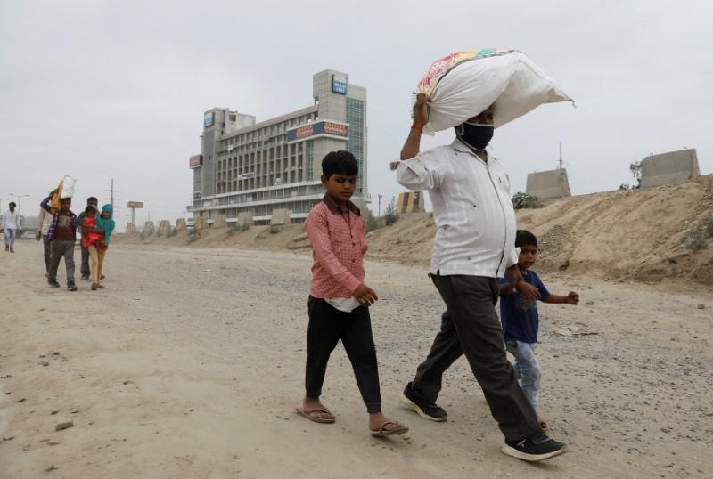 Migrant workers and their families walk on a highway as they look out for a transport to return to their villages, after India ordered a 21-day nationwide lockdown to limit the spreading of coronavirus disease (COVID-19), in Ghaziabad