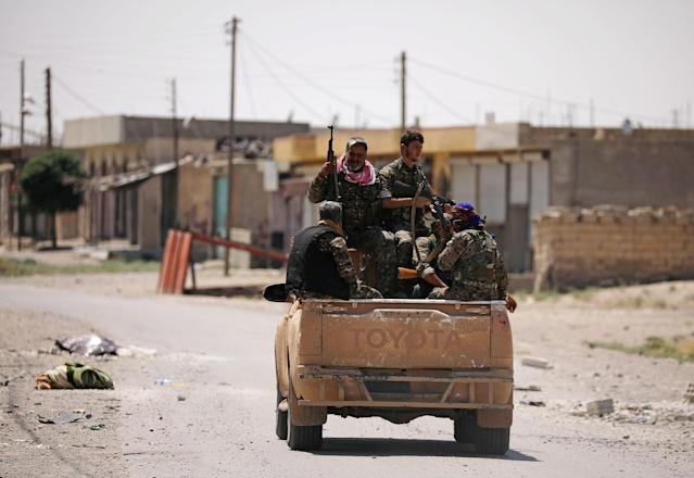 <p>Syrian Democratic Forces (SDF) fighters ride on a pick-up truck along a street in Raqqa's western neighbourhood of Jazra, Syria June 11, 2017. (Photo: Rodi Said/Reuters) </p>