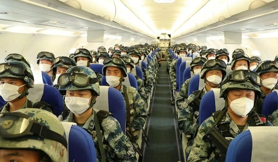 Pictured are dozens of Chinese military personnel on a plane.