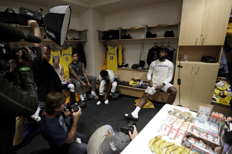 Los Angeles Lakers forward LeBron James, right, sits in the locker room before an NBA preseason basketball game against the Denver Nuggets Sunday, Sept. 30, 2018, in San Diego. (AP Photo/Gregory Bull)