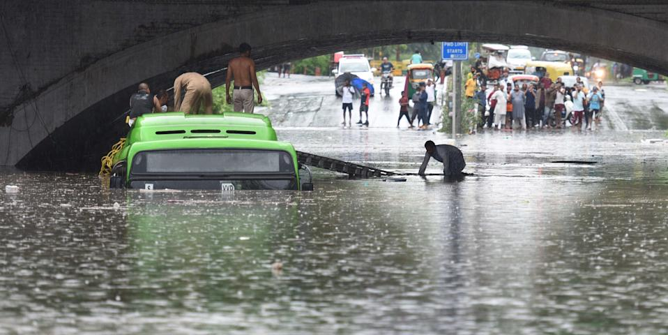 NEW DELHI, INDIA JULY 19: A man is rescued after his vehicle was submerged following heavy rain and waterlogging under the Minto Bridge, on July 19, 2020 in New Delhi, India. Moderate-to-heavy rain lashed several states in northern, eastern and coastal India on Sunday, but the monsoon activity continued to remain subdued in Delhi, which has recorded a 40 per cent rainfall deficiency despite an early onset of the seasonal weather system. (Photo By Arvind Yadav/Hindustan Times via Getty Images)