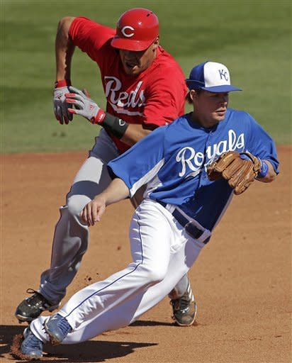 Cincinnati Reds' Donald Lutz, left, tries to get past Kansas City Royals second baseman Chris Getz while advancing to third on a throwing error by Salvador Perez after stealing second during the fourth inning of an exhibition spring training baseball game on Friday, March 1, 2013, in Surprise, Ariz. (AP Photo/Charlie Riedel)