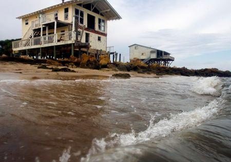 Waves crash onto the shore near an abandoned beach house (L) on the Gulf Coast in Alligator Point, Florida, July 9, 2014. Picture taken July 9. 2014. REUTERS/Phil Sears
