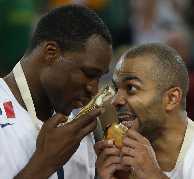 France's Tony Parker, right, reacts with France's Florent Pietrus, left, after receiving their gold medals for winning the EuroBasket European Basketball Championship in Ljubljana, Slovenia, Sunday, Sept. 22, 2013. France defeated Lithuania in their gold medal match 80-66. (AP Photo/Petr David Josek)
