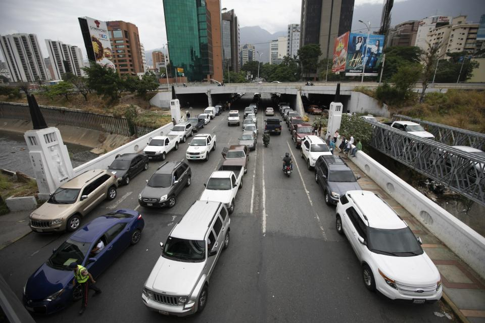 Vehicles line up near a gas station to fill their tanks, in Caracas, Venezuela, Friday, May 29, 2020. Venezuela boasts the world's largest underground oil reserves, but it has been forced to buy fuel from Iran to bridge deep shortages, unable to pump crude from the ground and turn it into gasoline. (AP Photo/Ariana Cubillos)