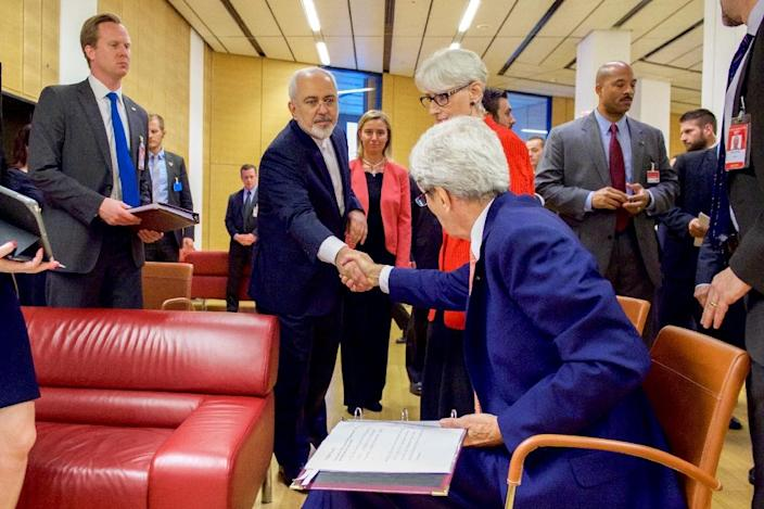 US Secretary of State John Kerry shakes hands with Iranian Foreign Minister Javad Zarif as he prepares to leave the Austria Center in Vienna, Austria, on July 14, 2015 (AFP Photo/)