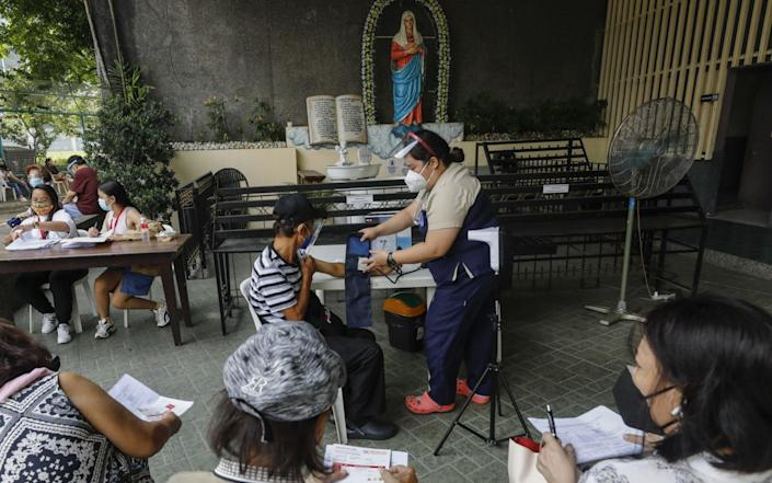 A nurse prepares to administer doses of the Covid-19 vaccine at a Catholic church in Quezon City, Philippines on 13 August 2021 - Rolex Dela Pena/Shutterstock
