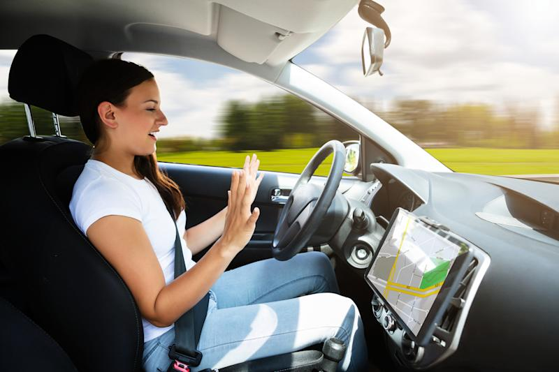 A woman taking her hands off the wheel of a driverless car