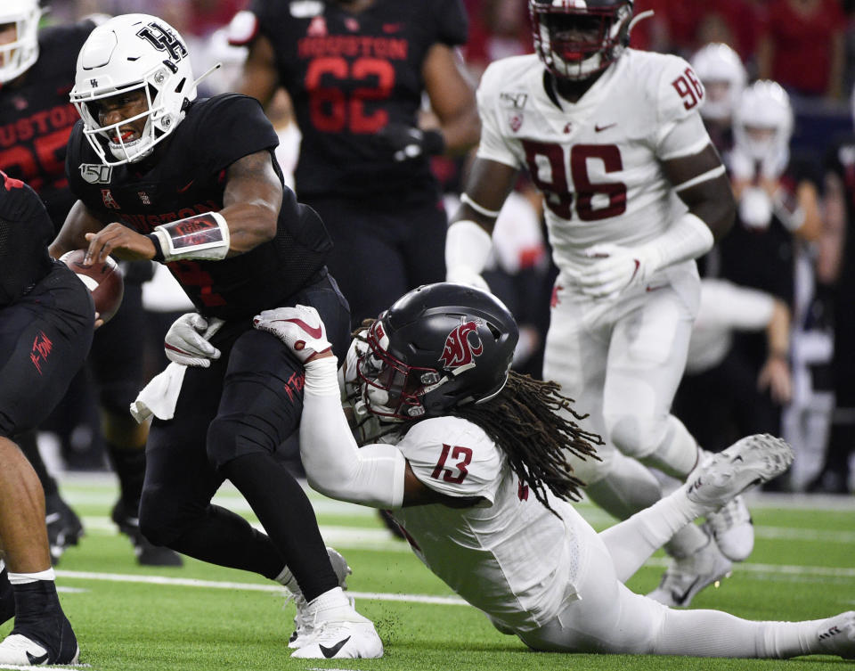 Houston quarterback D'Eriq King, left, is tackled by Washington State linebacker Jahad Woods (13) during the first half of an NCAA college football game Friday, Sept. 13, 2019, in Houston. (AP Photo/Eric Christian Smith)