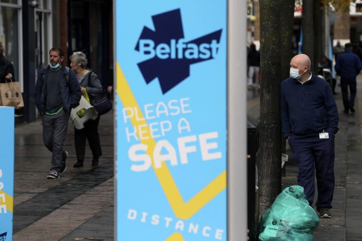 """A man wears a face mask in Belfast city centre, Northern Ireland, Wednesday, Oct. 14, 2020. Northern Ireland introducing the tightest COVID-19 restrictions in the United Kingdom on Wednesday, closing schools for two weeks and pubs and restaurants for a month. """"This is not the time for trite political points,"""" First Minister Arlene Foster told lawmakers at the regional assembly in Belfast. """"This is the time for solutions."""" (Brian Lawless/PA via AP)"""