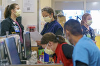 """""""It's devastating, and really heartbreaking knowing people are fighting for their lives and it could have been prevented,"""" says charge nurse Erin Boni, center, at Oregon Health and Science University's intensive care unit in Portland, Ore., Thursday, Aug. 19, 2021. The hospital's ICU units are filled to capacity but the phone calls asking for help keep coming from rural Oregon hospitals. (Kristyna Wentz-Graff/Pool Photo via AP)"""