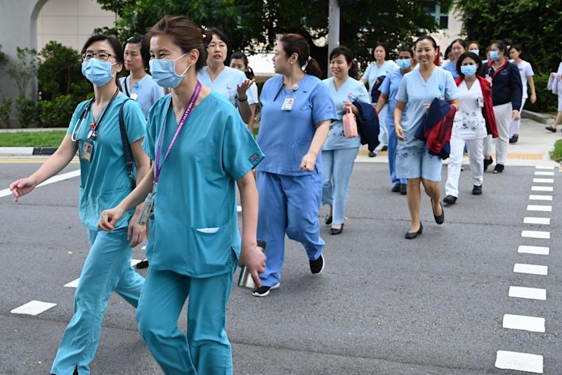 Medical staff walk to the National Centre for Infectious Diseases building at Tan Tock Seng Hospital in Singapore on January 31, 2020. - Patients infected with the virus similar to the SARS pathogen are warded in isolation rooms at the National Centre for Infectious Diseases according to the health ministry as Singapore bans January 28 new arrivals with recent travel to virus-hit Chinese province ramping up government measures against the spread of a deadly virus. (Photo by Roslan RAHMAN / AFP) (Photo by ROSLAN RAHMAN/AFP via Getty Images)