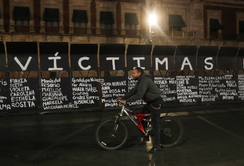 A man rides a bicycle past the names of victims of femicide in Mexico painted by women on fences placed outside the National Palace ahead of a Women's Day protest, in Mexico City