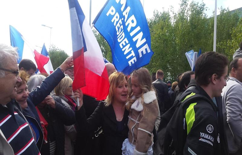 A Marine Le Pen supporter holds her daughter at Marine Le Pen's rally (The Independent)