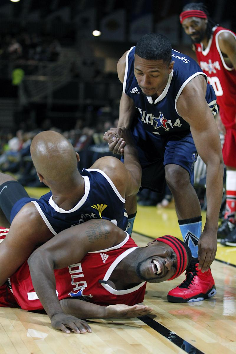 East's Nick Cannon, front left, reaches for West's Kevin Hart, bottom, as East's Bruce Bowen, top left, gets up in the first half as they participate in the NBA All-Star Celebrity basketball game in New Orleans, Friday, Feb. 14, 2014. East won 60-56. (AP Photo/Bill Haber)