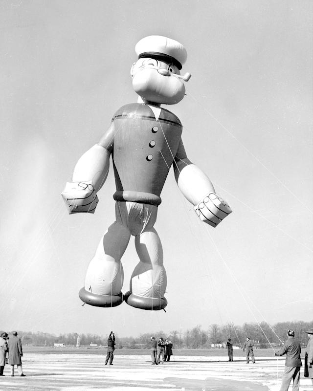 <p>Popeye, the sailor, flexes his muscles as he gets ready to parade in Macy's Thanksgiving Day parade in 1957. Popeye stands 56 feet tall, 32 feet wide and he's filled with 6,000 cubic feet of helium. (Photo: New York Daily News Archive via Getty Images) </p>