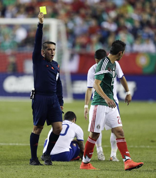 Mexico defender Paul Aguilar, right, is penalized with a yellow card after knocking Portugal forward Vierinha to the turf during the first half of their friendly soccer match in Foxborough, Mass., Friday, June 6, 2014. (AP Photo/Charles Krupa)