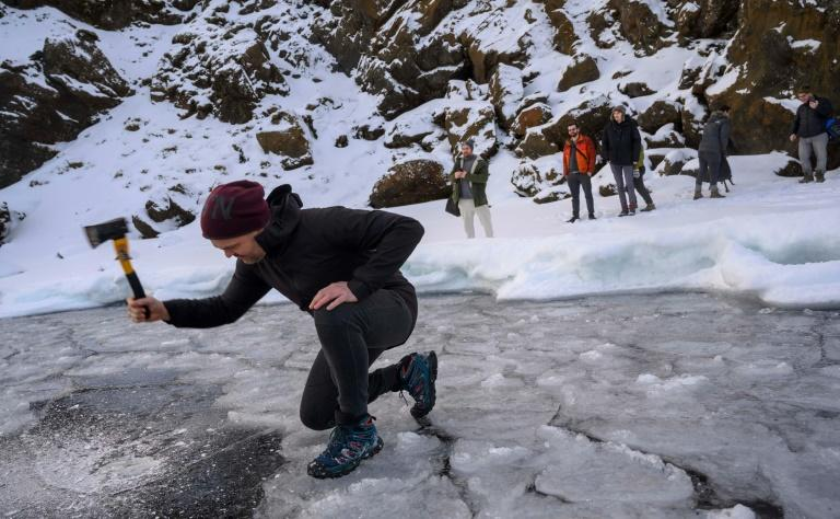 Andri Einarsson, co-instructor on the cold bathing seminar, cuts a hole through the sheet of ice covering the lake (AFP Photo/Halldor KOLBEINS)