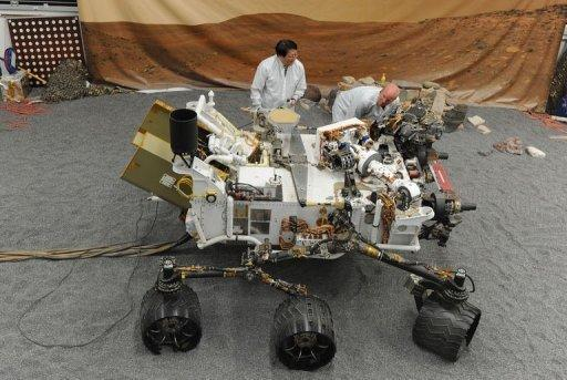 """Jet Propulsion Laboratory (JPL) engineers examine a full size engineered model of the Mars rover Curiosity, on August 2. About 36 hours after the US space agency's landed its $2.5 billion rover on Mars, NASA released Tuesday what it called a """"crime scene"""" aerial shot of where the parachute, heat shield and rover came down"""